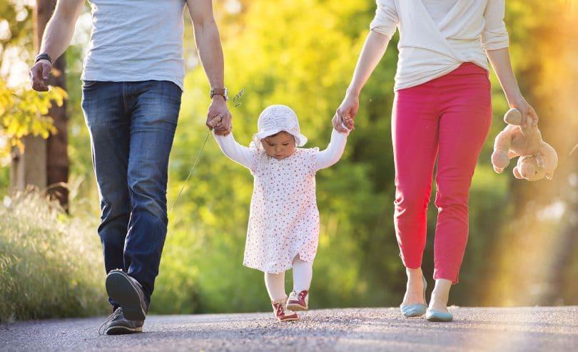 Pais e filhos andando de mãos dadas.