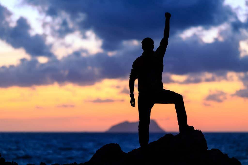 Silhueta de pessoa comemorando levantando um de seus braços, em pé em cima de uma pedra, observando o pôr do sol no mar.