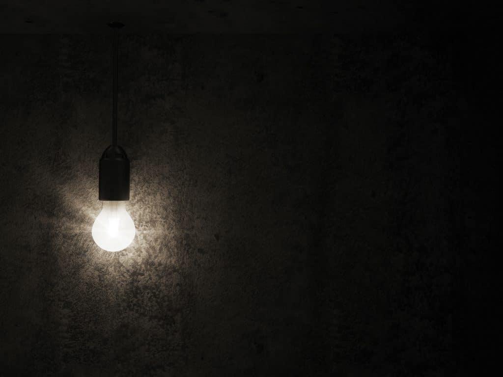 Lampada acesa, emanando luz branca, em um ambiente completamente apagado e preto.