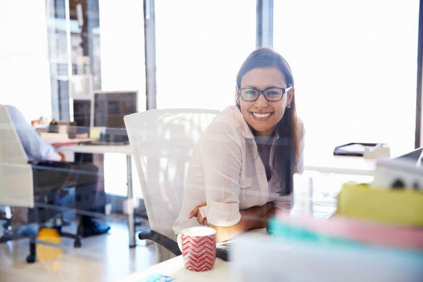 Mulher em seu escritório sorrindo para a câmera