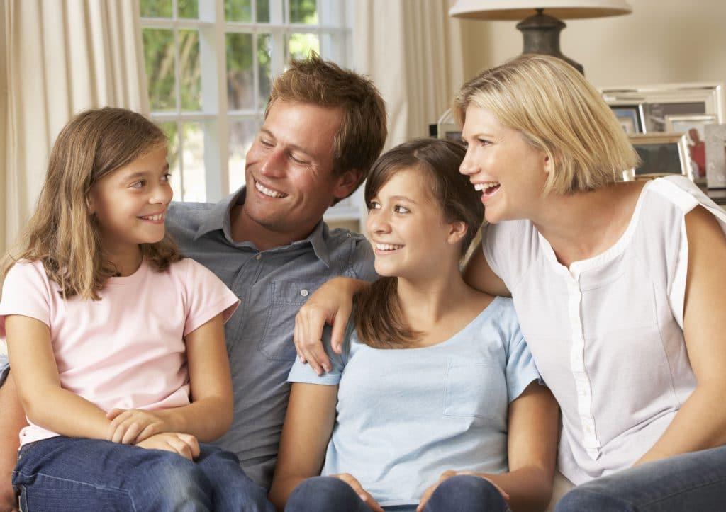 Pais e filhos sentados no sofá conversando.