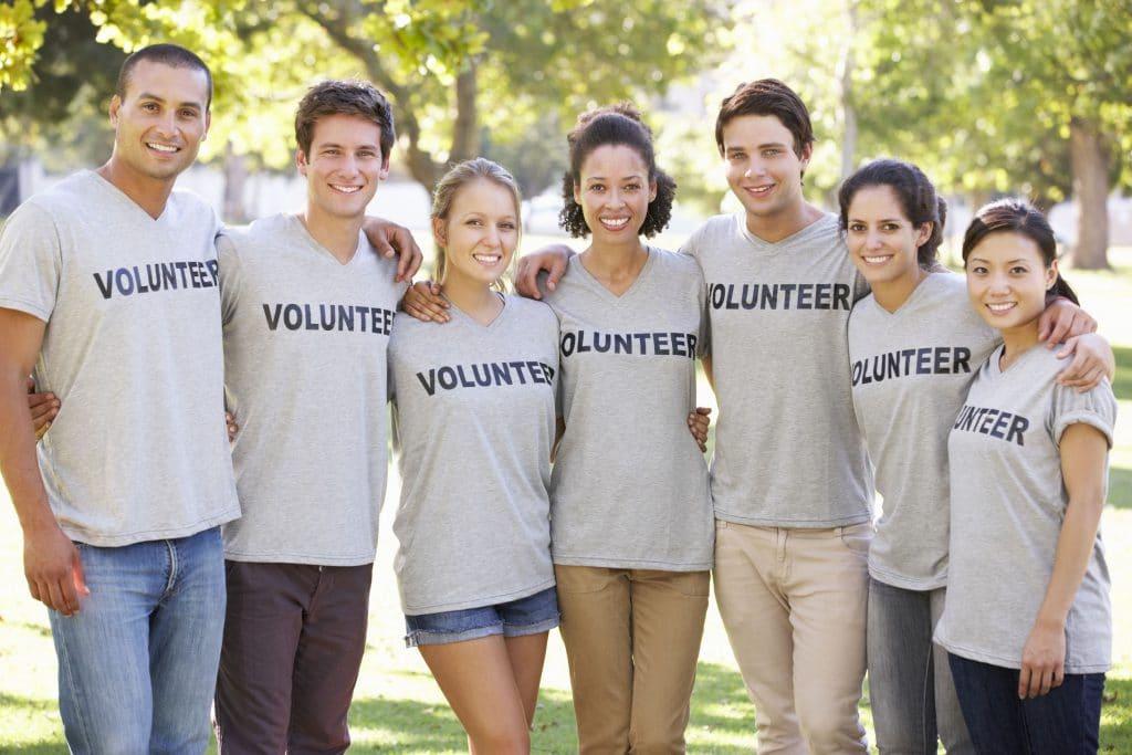 Grupo de pessoas de diversas etnias, todos sorrindo e vestindo camisetas cinzas, com a palavra voluntário escrito.