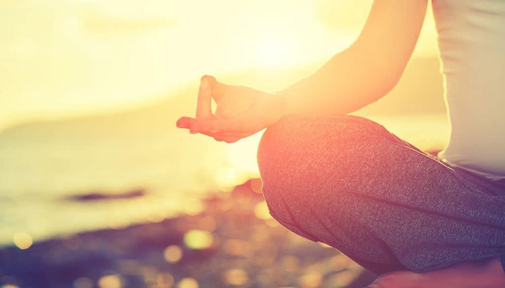 Pessoa sentada com as pernas cruzadas, apoiando as mãos nos joelhos, meditando na praia durante um pôr do sol com o mar ao fundo.
