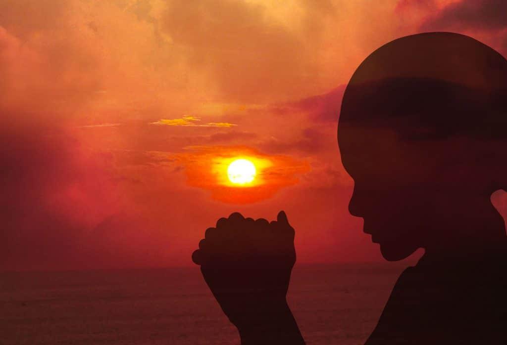 Mulher orando em frente ao pôr-do-sol
