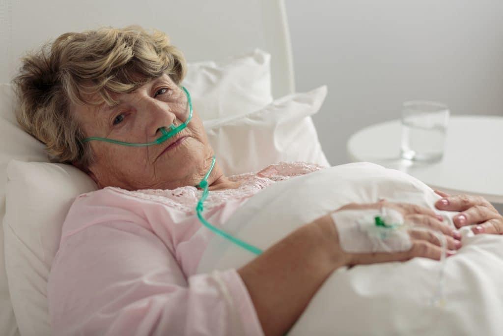 Mulher branca, idosa, deitada em cama de hospital.