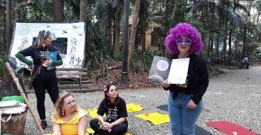 Foto da colunista em meio de roda de contar histórias da Associação Viva e Deixe Viver.