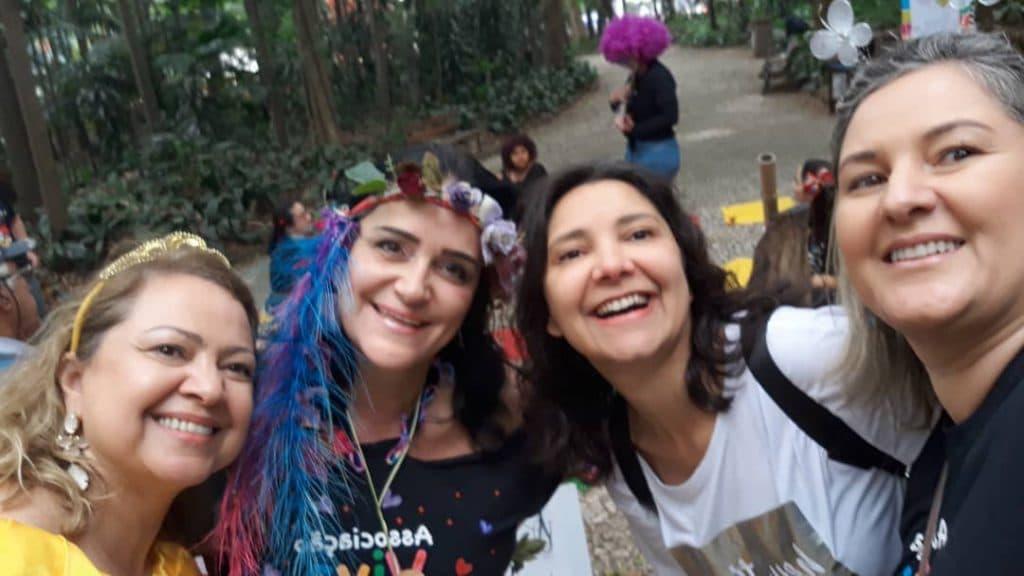 Foto da colunista com outros companheiras do grupo de trabalho voluntário, em um parque, durante um evento de leitura.