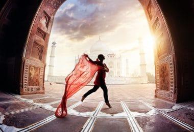 Silhueta de mulher dançando com um lenço vermelho em uma paisagem urbana.