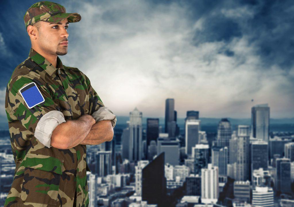 Homem vestido com farda militar. parado com os braços cruzados. Ao fundo há a paisagem de uma cidade.
