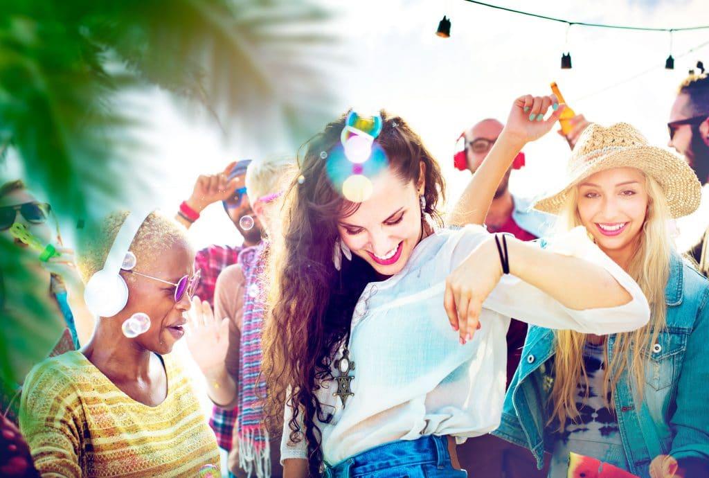 Pessoas de diversas etnias dançando em uma festa ao ar livre