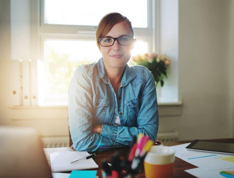 Mulher em escritório olhando diretamente para a câmera. Aparenta confiança e bom humor.