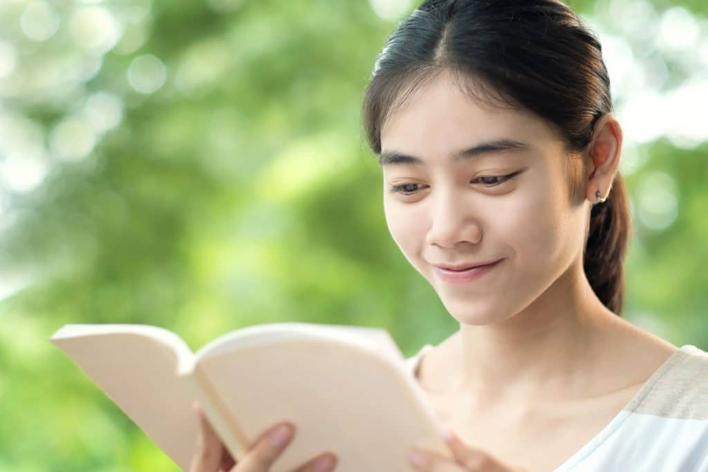 Mulher asiática lendo um livro, em pé em um parque
