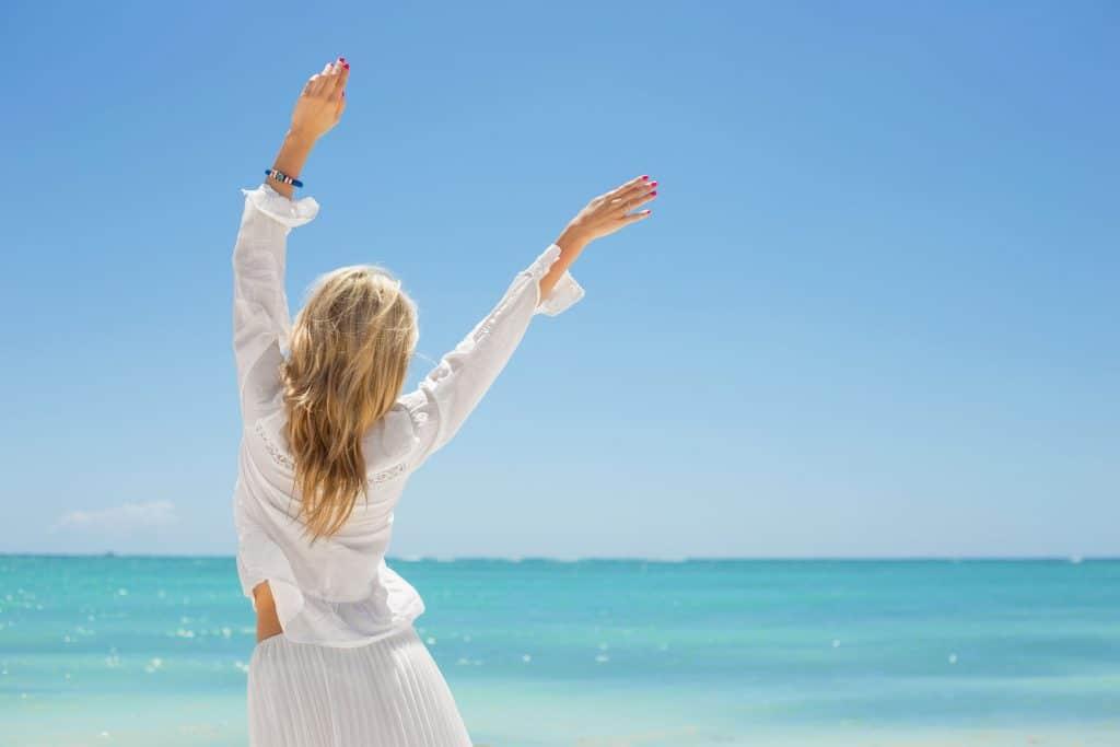 Mulher jovem e feliz na praia.