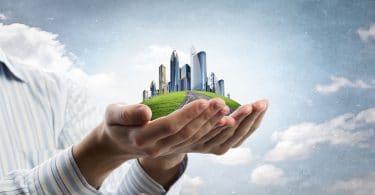 Mãos fechadas segurando a imagem de uma cidade moderna, sob fundo de céu.