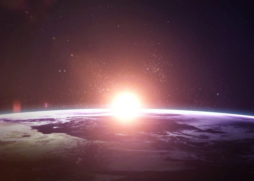 Terra no espaço com o sol surgindo