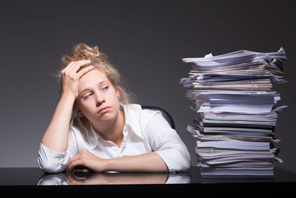 Mulher branca, com expressão de frustração e cansaço, apoiando-se em cima de uma mesa preta, ao lado de uma pilha de papéis.