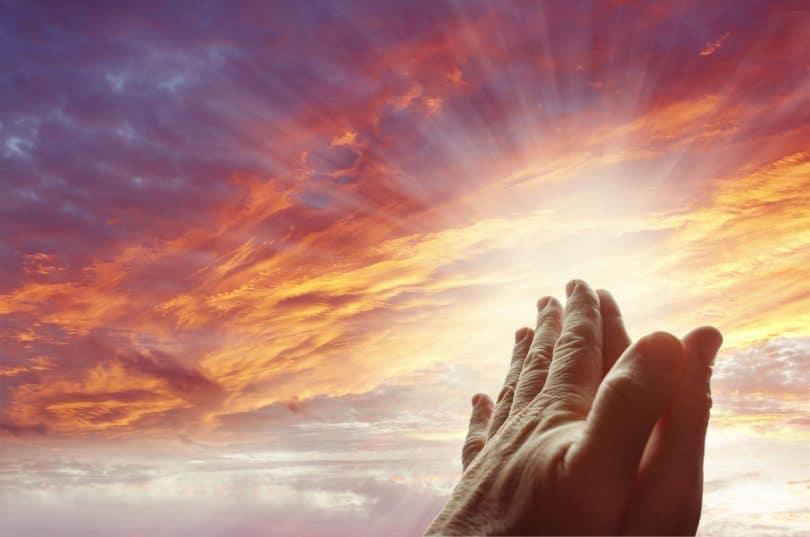 Mãos orando para céu brilhante.