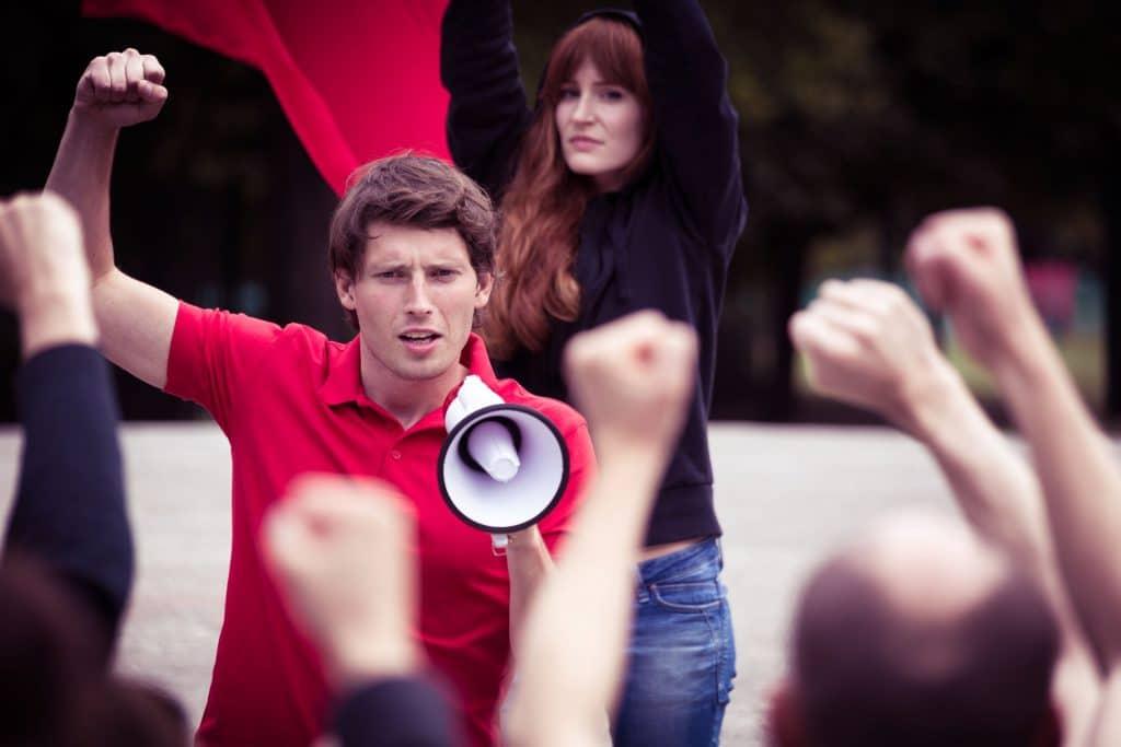 Representação do Eu cidadão: Homem vestido de vermelho segurando um megafone gritando em um protesto, com mulher vestida de preta, segurando um bandeirão vermelho, ao fundo.