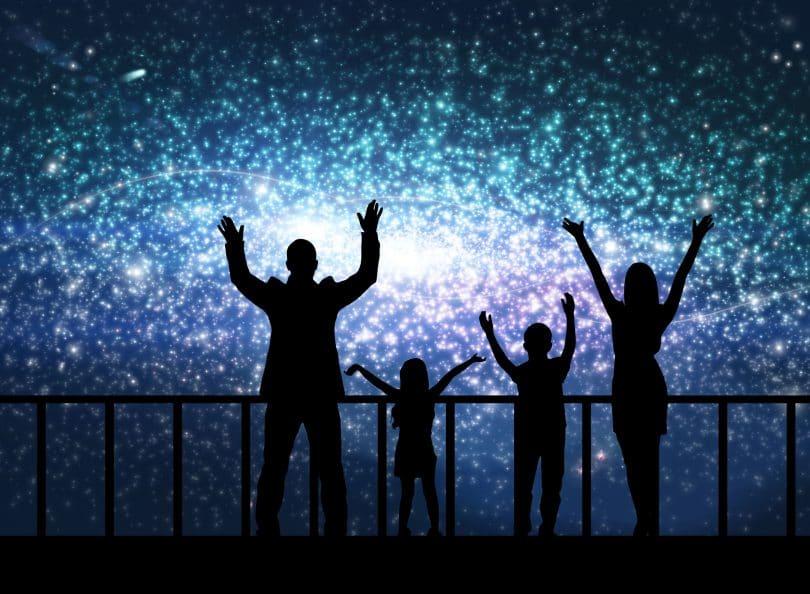 Silhueta de homem, mulher e duas crianças, representando o conceito de família, observando a pintura de uma constelação colorida. Representando o evento de Constelação familiar em grupo.