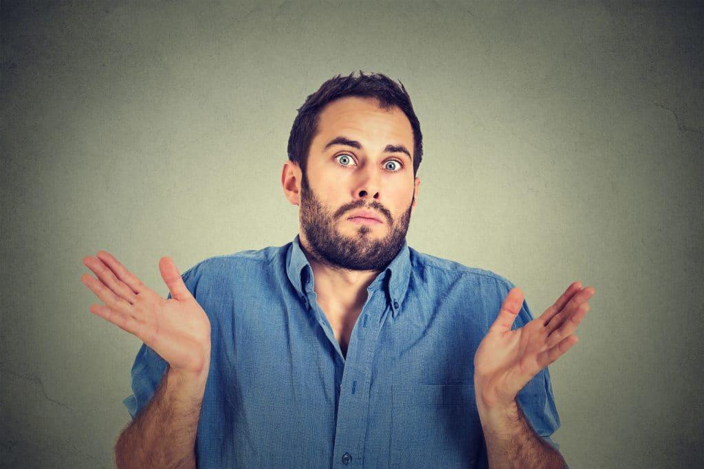 Homem fazendo cara de quesitonamento levantando os ombros e as mãos.