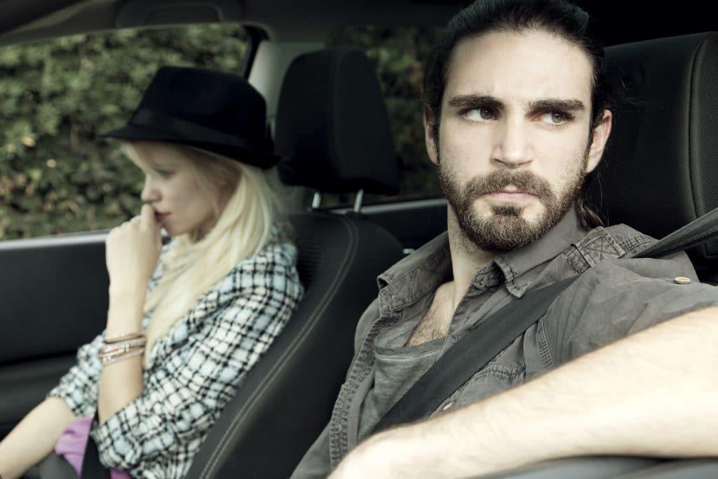 casal dentro do carro olhando em direções opostas depois de uma briga.