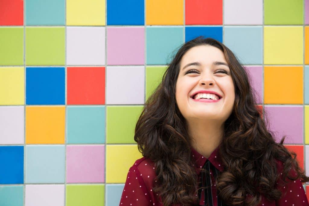 Mulher branca, jovem, sorridente, encostada em uma parede com azulejos coloridos.