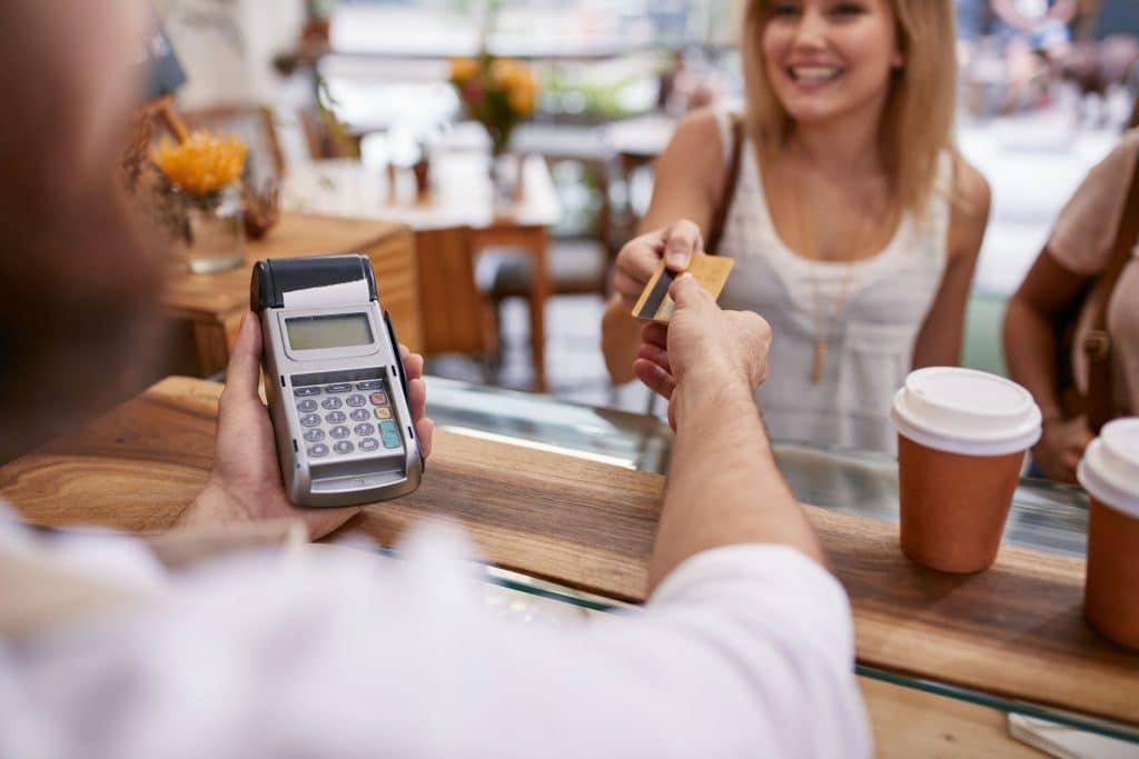 Cliente mulher pagando no cartão um café.