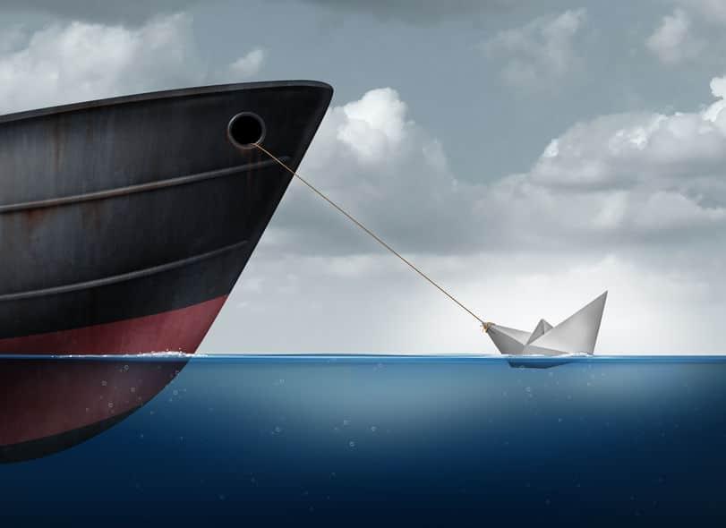 Barco de papel sobre o oceano sendo carregado por navio