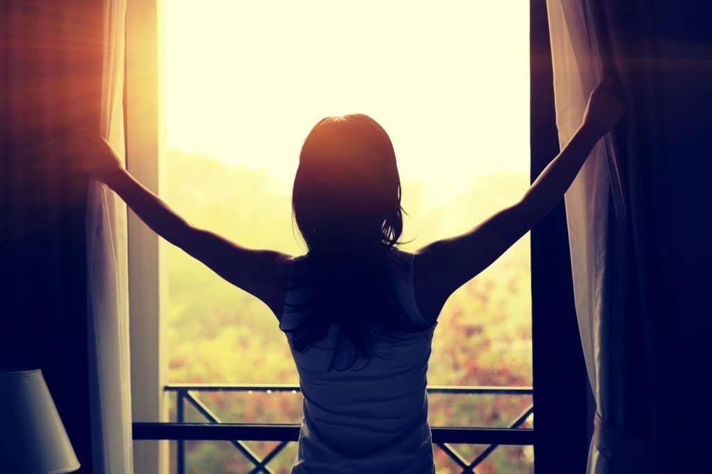 Silhueta de mulher abrindo as cortina de uma janela em um dia ensolarado