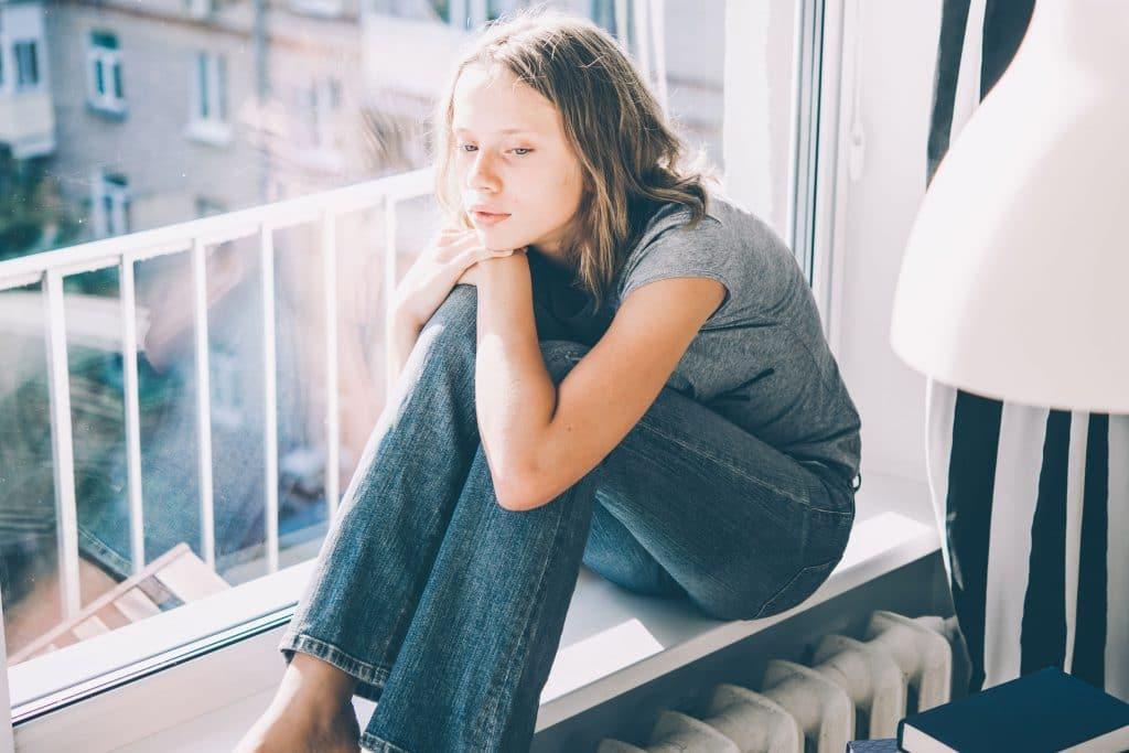 Menina triste sentada com os joelhos dobrados.