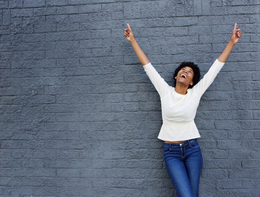 Mulher negra, vestindo jeans e camiseta branca, apoiada em uma parede de tijolos cinza, sorrindo e olhando para cima com os braços levantados.