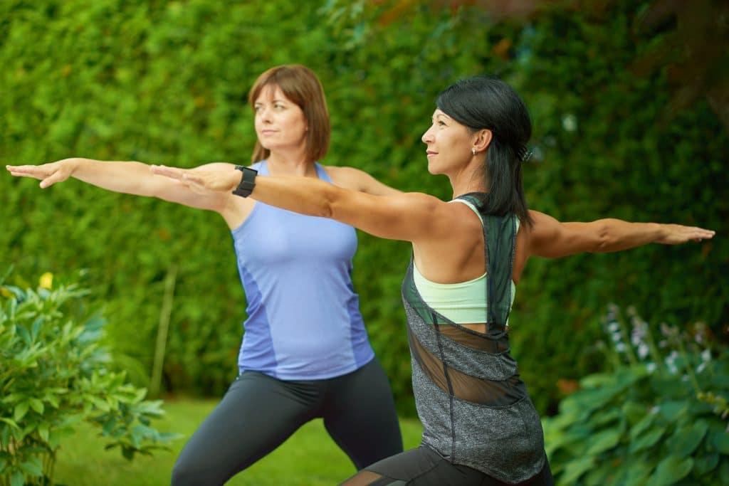 Duas mulheres, próximas aos 50 anos, praticando yoga