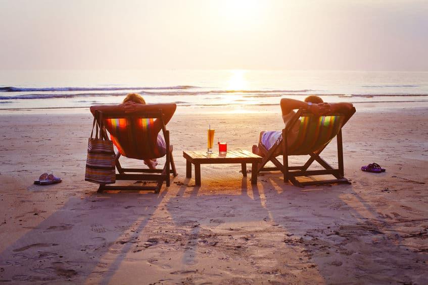 Duas pessoas relaxando em cadeiras de praia e olhando o mar
