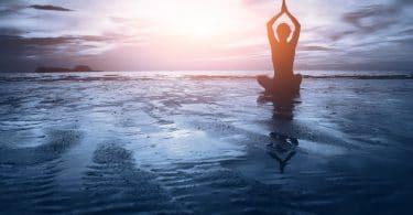 Silhueta de mulher praticando Yoga na praia de frente para o pôr do sol