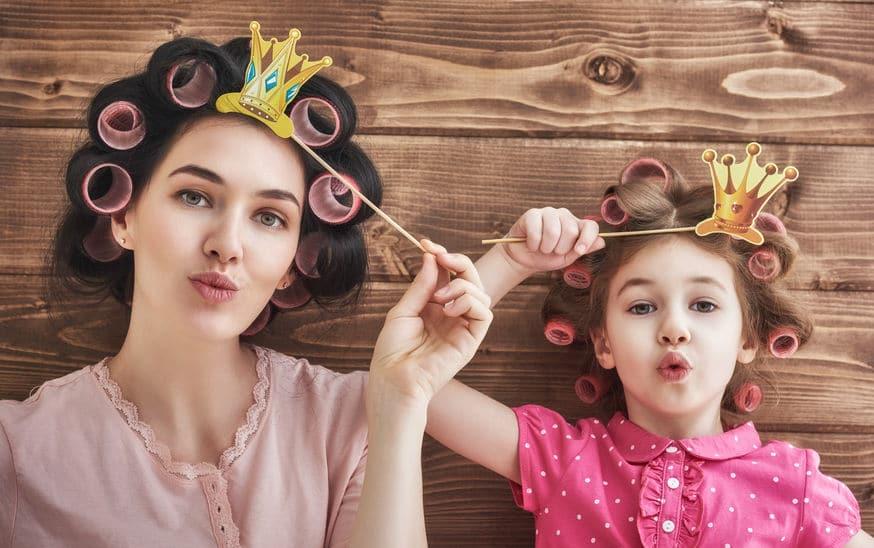 Mãe e sua filha criança com coroas de papel.