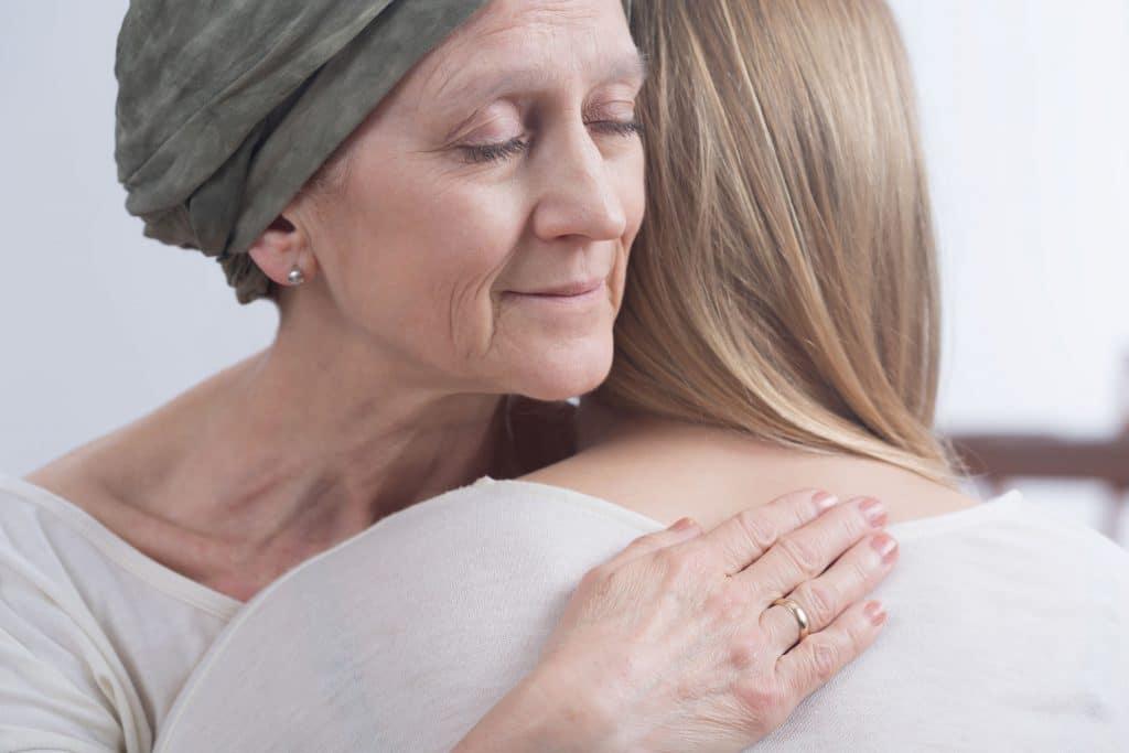 Mulher que tem câncer, com um lenço verde na cabeça, com o rosto sereno, abraçando sua filha, se despedindo.