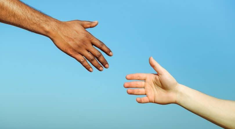 Duas mãos estendidas em sinal de ajuda.