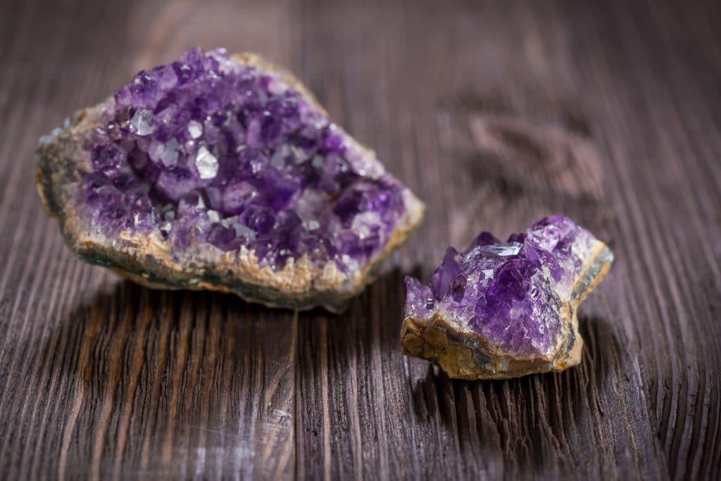 Duas pedras de Ametista natural em cima de uma mesa de madeira, uma grande e uma pequena.