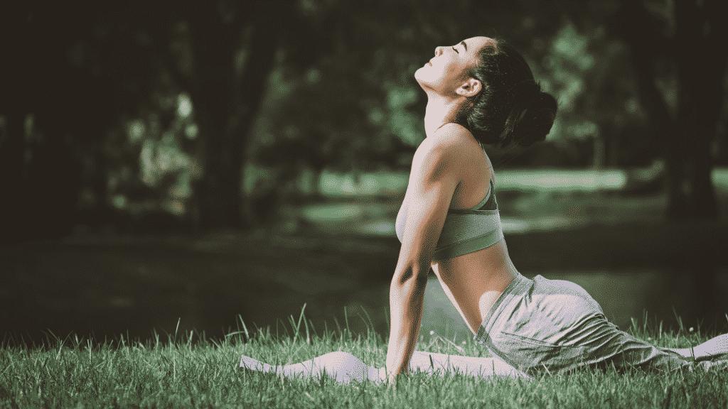 Mulher fazendo yoga no parque