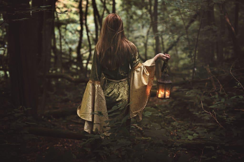 Mulher vestindo um vestido de princesa medieval andando na floresta com um lanterna na mão.