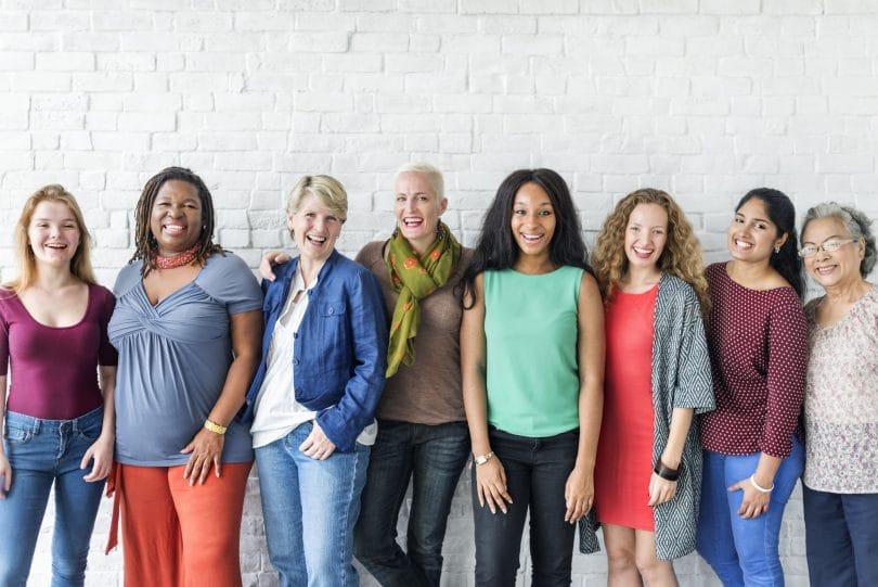Mulheres de diversas etnias, com corpos diferentes, todas sorridentes, posando em frente de uma parede de tijolos brancos.