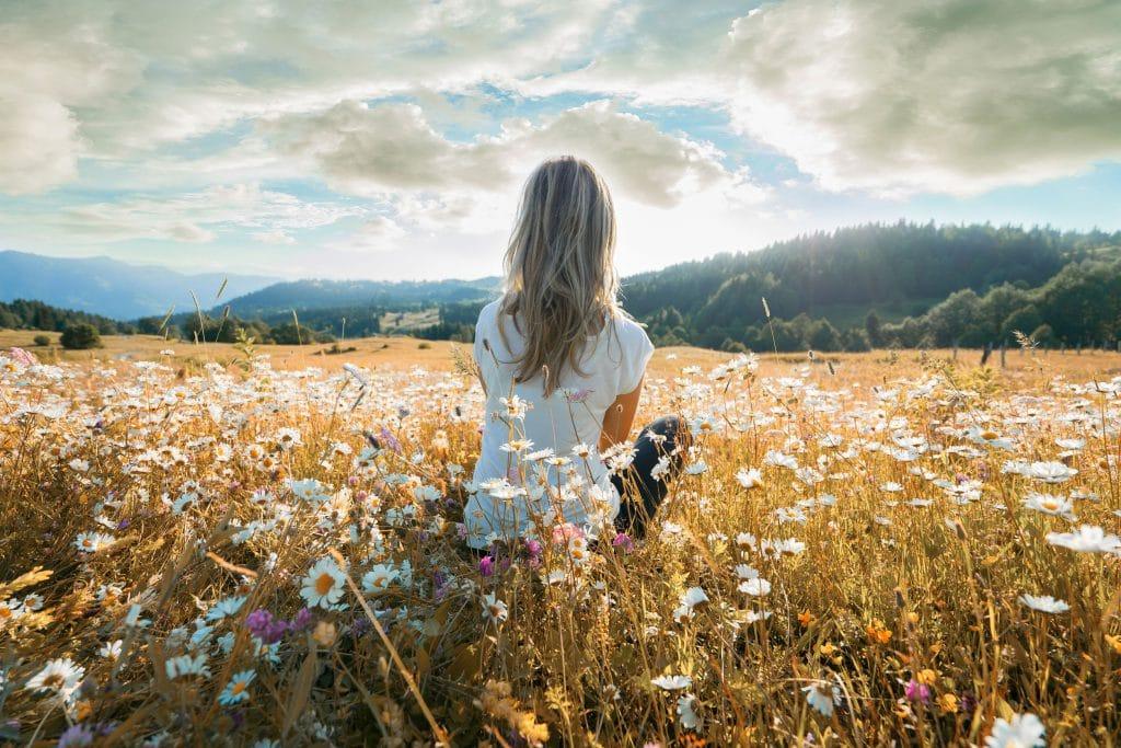 mulher sentada em campo de margaridas, observando paisagem de montanhas em um dia ensolarado.