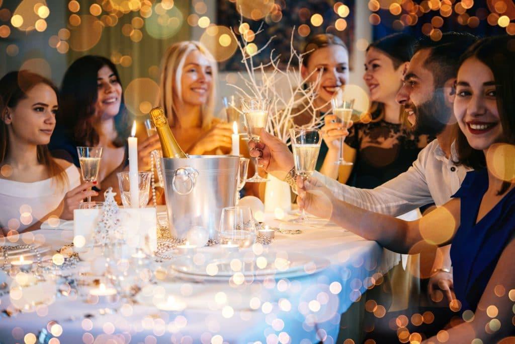 Pessoas de diversas etnias sentados em uma mesa branca, decorada para festa com coisas douradas. Cada pessoa segura uma taça de champanhe para brindar.