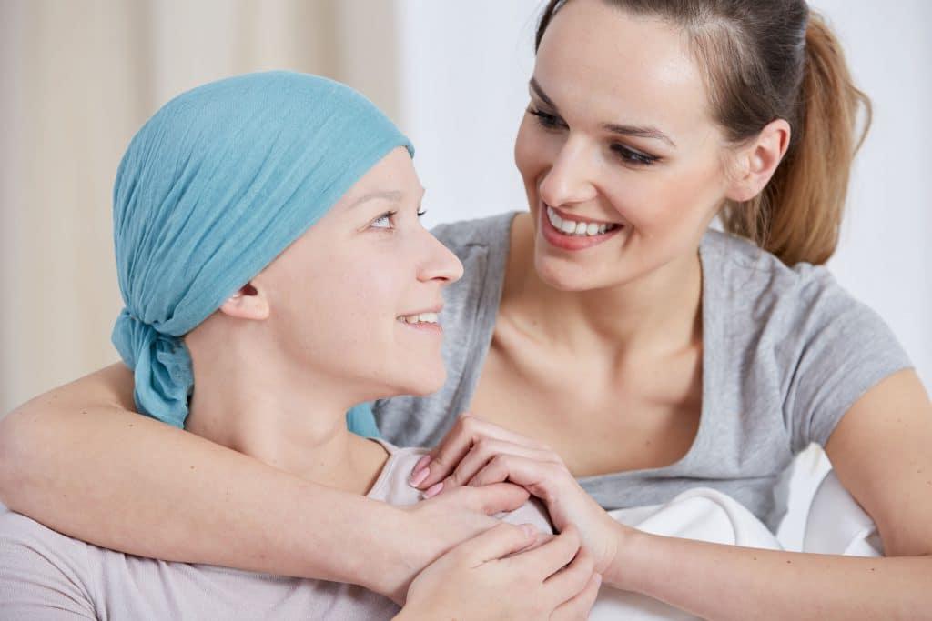 Mulher sorridente abraçando por trás a sua mãe que tem câncer e usa um lenço na cabeça, mas também sorri.