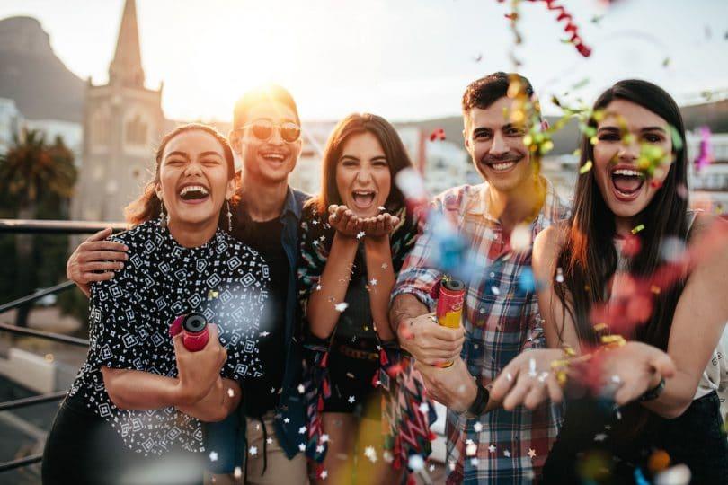 Turma de amigos em folia jogando confete na câmera.