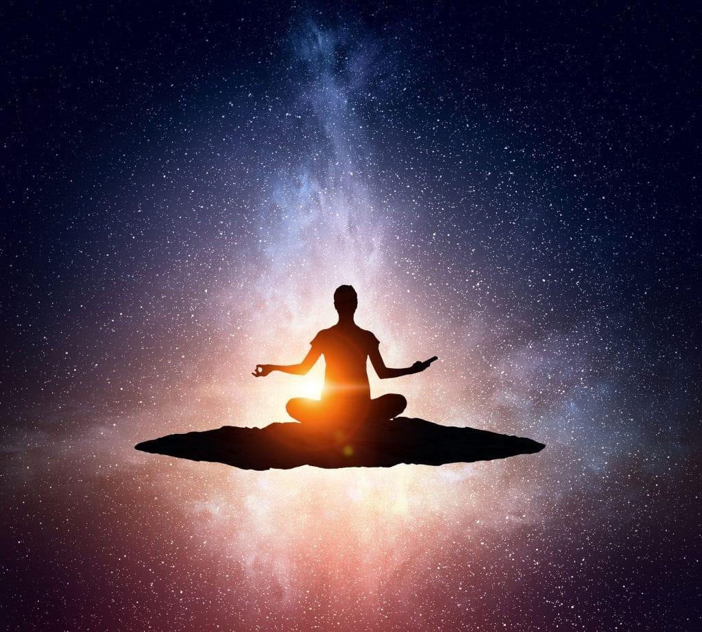 Silhueta de mulher meditando no espaço.