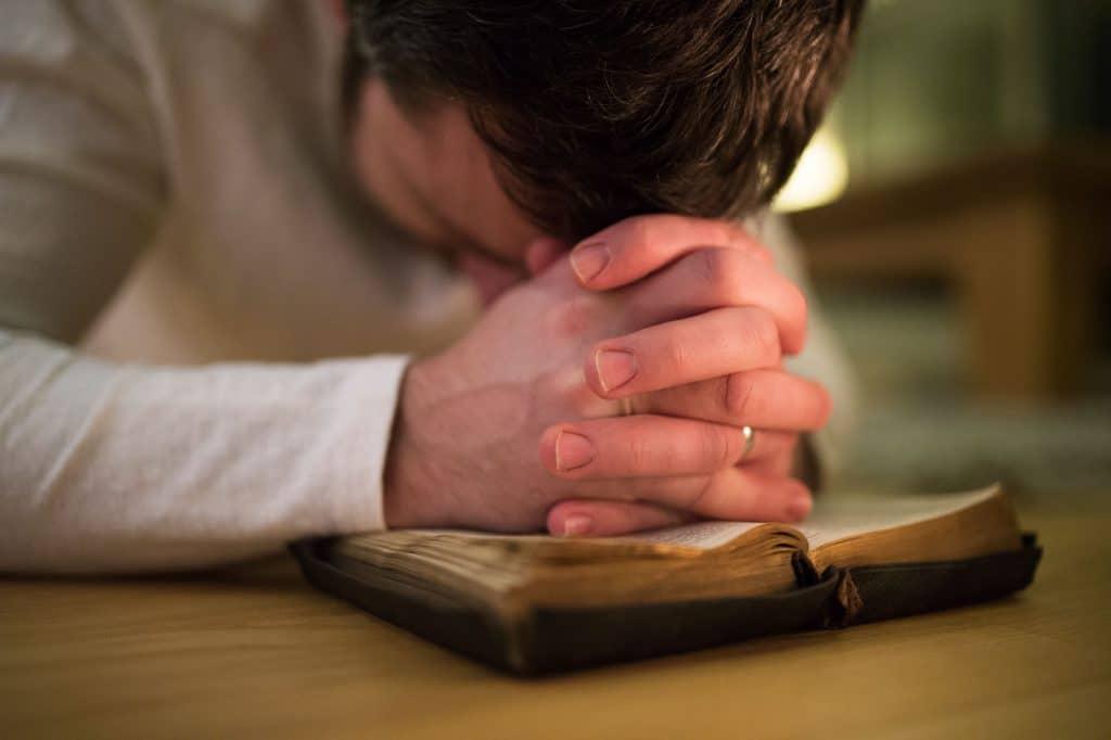 Homem prostrado em cima de uma bíblia.