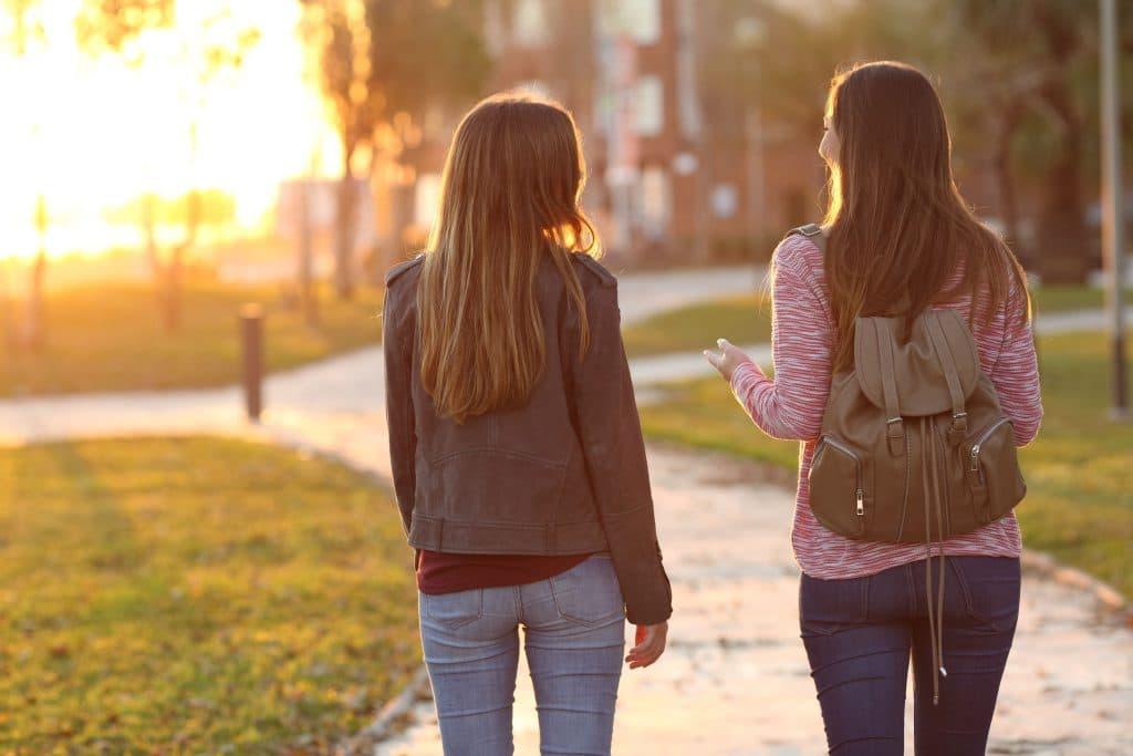 Amigas conversando enquanto andam em parque.