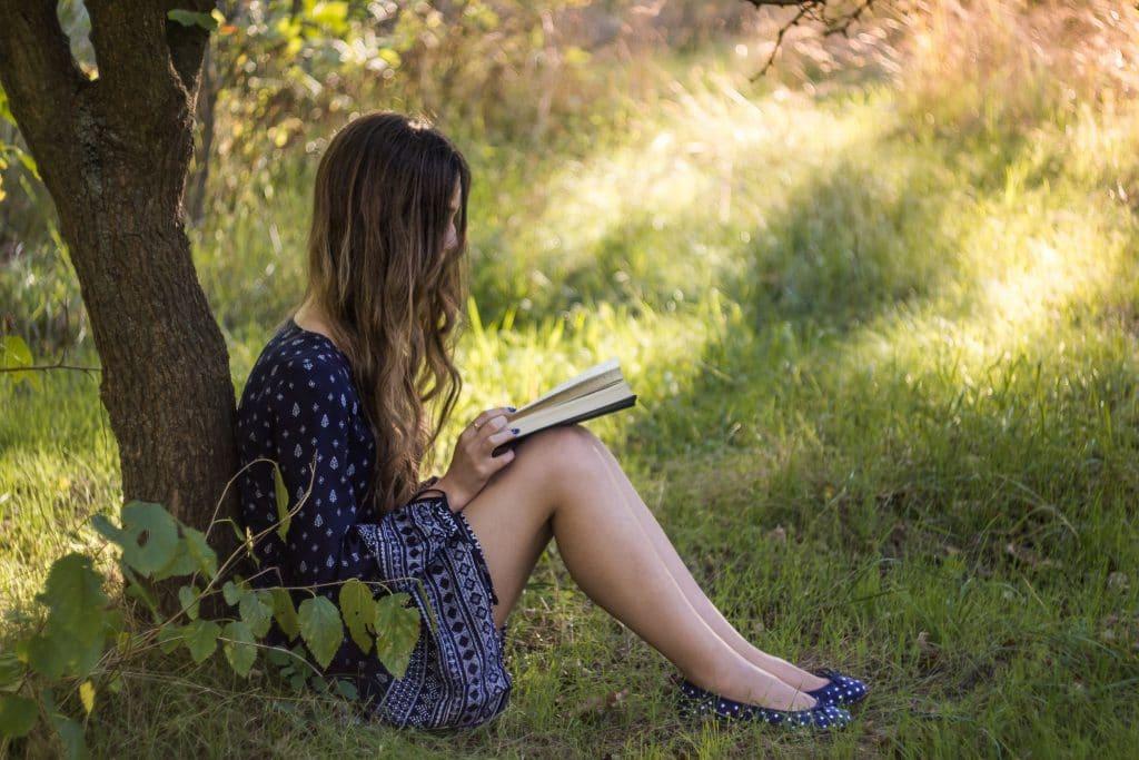 Mulher sentada embaixo de uma árvore, lendo um livro.