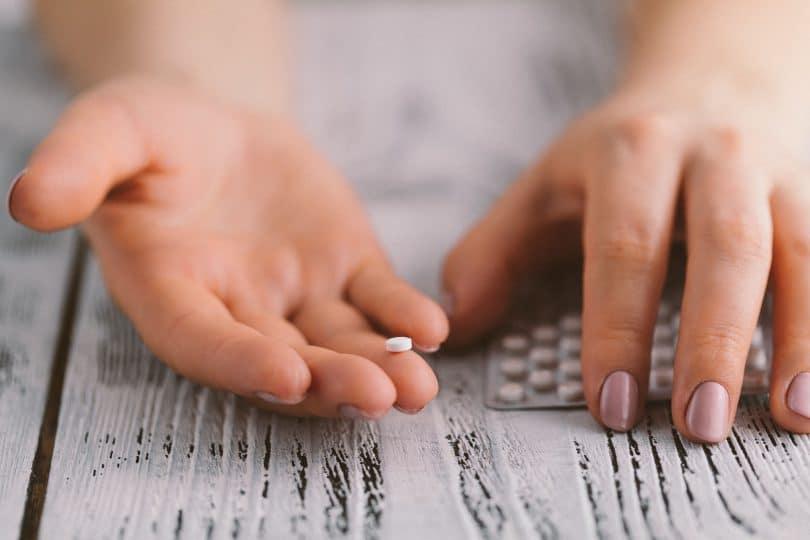 Close de mãos de mulher, uma segurando uma cartela de anticoncepcionais e outra segurando uma pílula sozinha.